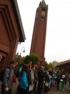 Schülerinnen und Schüler mit ihren Entdeckerbögen vor dem Kirchengebäude